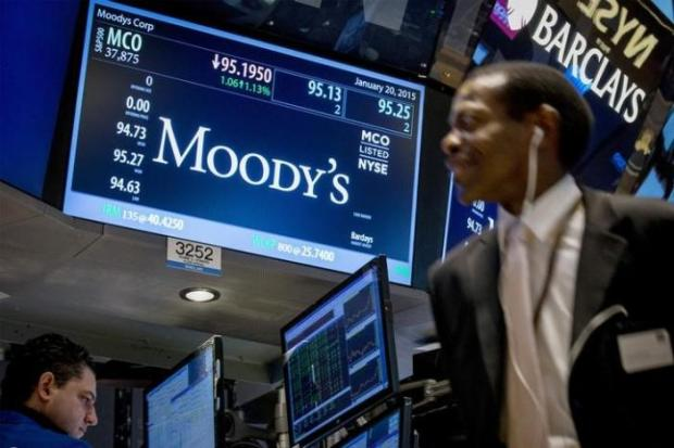 A screen displays Moody's ticker information as traders work on the floor of the New York Stock Exchange